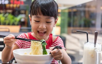 Image: Happily-eating-noodles---Young-girl---The-Confident-Eater